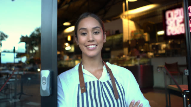 Beautiful business owner of her bakery standing leaning on the entrance with arms crossed smiling Beautiful business owner of her bakery standing leaning on the entrance with arms crossed smiling at camera owner stock videos & royalty-free footage