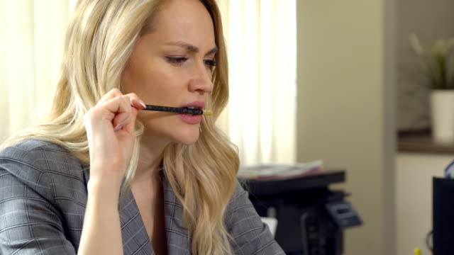 vídeos de stock e filmes b-roll de beautiful business woman biting her pencil in office. - caneta