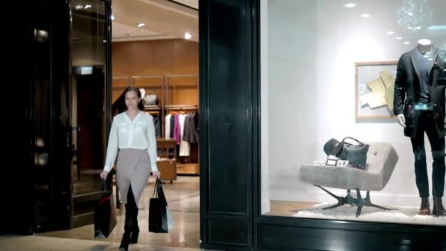 vídeos de stock, filmes e b-roll de mulher de negócios bonito carregando sacolas de compras enquanto caminhava ao longo do mall, em traje de luxo - extravagância
