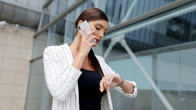 Beautiful Business Woman Talking On Phone Going To Work Beautiful Business Woman Talking On Phone Going To Work, Walking Near Office And Checking Time Outdoors checking the time stock videos & royalty-free footage