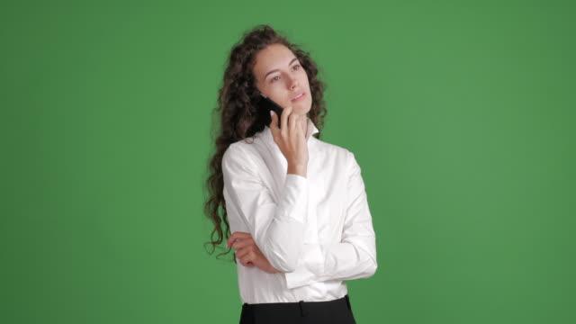 hermosa empresaria hablando airadamente en un smartphone en un fondo verde - vídeo