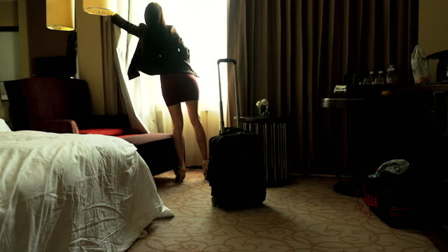 Beautiful businesswoman arriving in a hotel bedroom. video