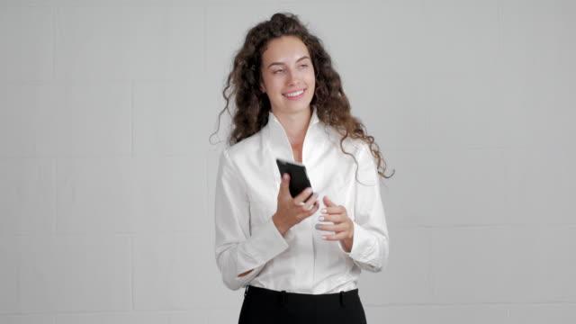 hermosa empresaria trae un smartphone en su cabeza y comienza a hablar sobre un fondo verde - vídeo