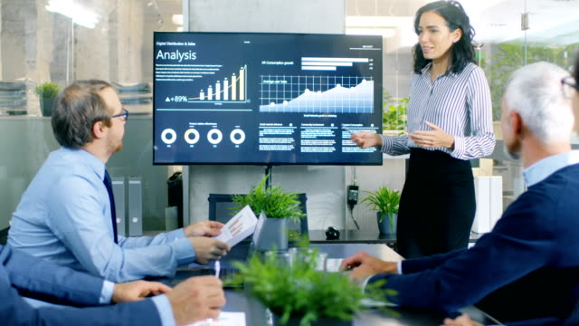 beautiful businesswoman gives report/ presentation to her business colleagues in the conference room, she shows graphics, pie charts and company's growth on the wall tv. - korporacja filmów i materiałów b-roll