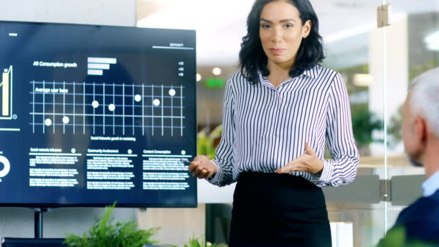 beautiful businesswoman gives report/ presentation to her business colleagues in the conference room, she shows graphics, pie charts and company's growth on the wall tv. - praca w sektorze handlowym filmów i materiałów b-roll