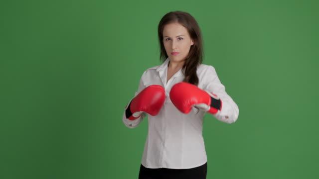 hermosa empresaria en guantes de boxeo divertidos muestra su victoria en un duelo en un fondo verde - vídeo