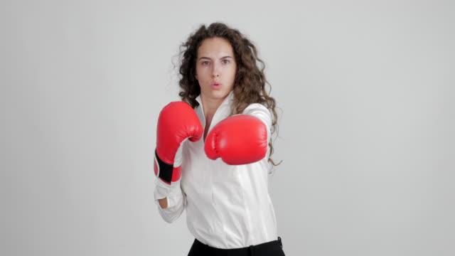 hermosa empresaria en guantes de boxeo divertidos muestra su victoria en un duelo sobre un fondo blanco - vídeo