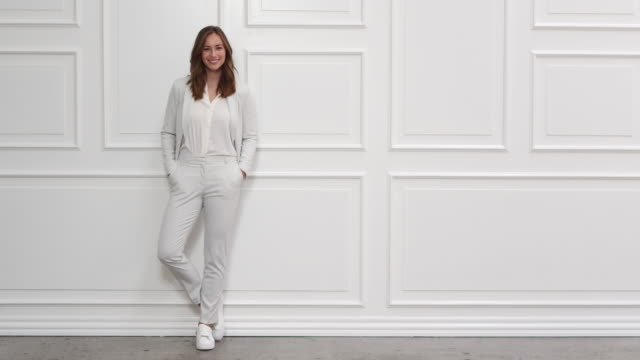 Beautiful Businesswoman In White Lockdown Wide Shot Of Beautiful Businesswoman In White Suit Looking To Wall Then To Camera physical position stock videos & royalty-free footage