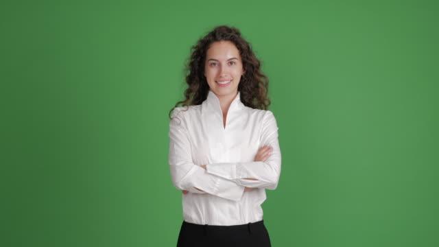 hermosa empresaria mirando con una sonrisa a la cámara con las manos cruzadas sobre un fondo verde - vídeo