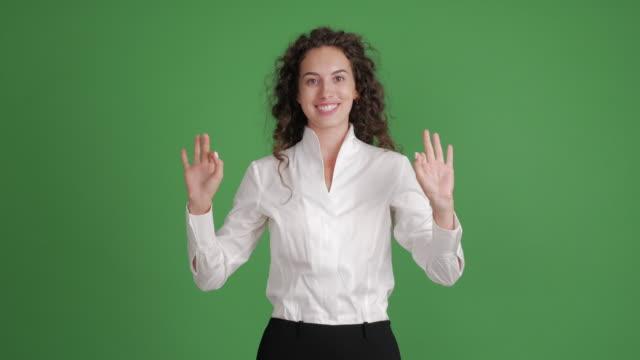 hermosa empresaria realizando una presentación de algo sobre un fondo verde - vídeo