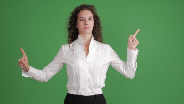 hermosa empresaria mostrando copia espacio y mostrando un tabú sobre fondo verde - vídeo