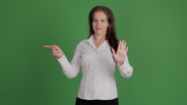 hermosa empresaria mostrando copia espacio y mostrando tabú sobre fondo verde - vídeo