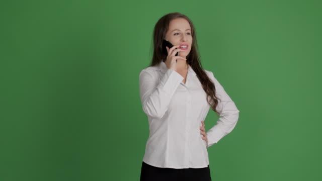hermosa empresaria hablando por un teléfono inteligente en un fondo verde - vídeo