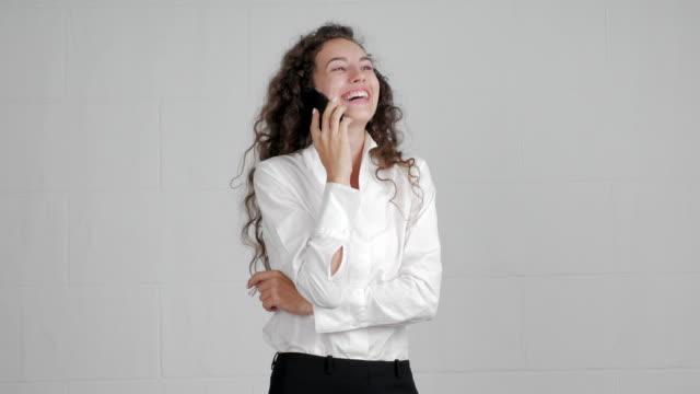 hermosa empresaria hablando por un teléfono inteligente en un fondo blanco - vídeo