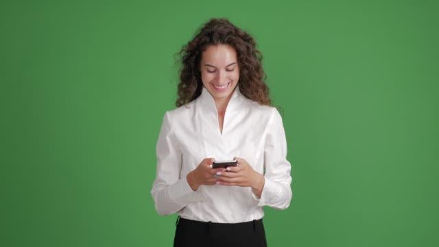 hermosa empresaria se utiliza para escribir mensajes en un teléfono inteligente en un fondo verde - vídeo