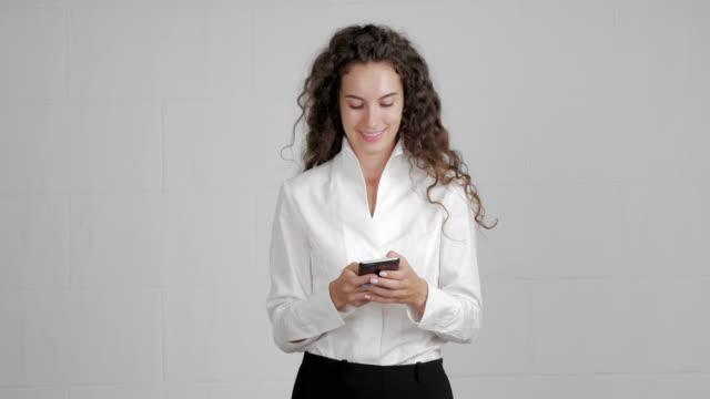 hermosa empresaria se utiliza para escribir mensajes en un teléfono inteligente en un fondo blanco - vídeo