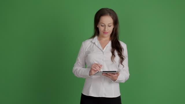 hermosa empresaria se utiliza para escribir mensajes en un tablet en un fondo verde - vídeo