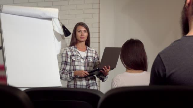 Hermosa mujer de negocios usando su computadora portátil durante la conferencia - vídeo