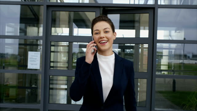 Beautiful businesswoman using smart phone while leaving from office video