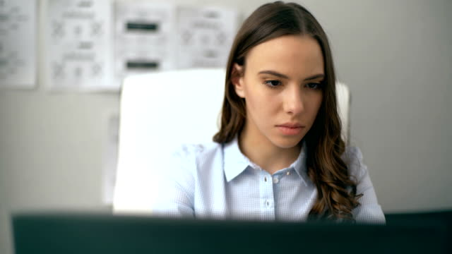 Beautiful businesswoman working on her laptop while sitting at office video