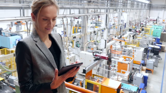 Beautiful businesswoman working on tablet in futuristic factory 4k high angle view video of young businesswoman working with digital tablet and examining the large futuristic factory. Woman standing on top of a balcony, holding touchpad and checking inventory of a manufacturing company on touchscreen tablet. Businesswoman's hands holding black tablet, futuristic machines in background. satisfaction stock videos & royalty-free footage