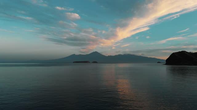 красивый спокойный океан с вулканом маунтин-вью на восходе солнца 2 - спокойная вода стоковые видео и кадры b-roll