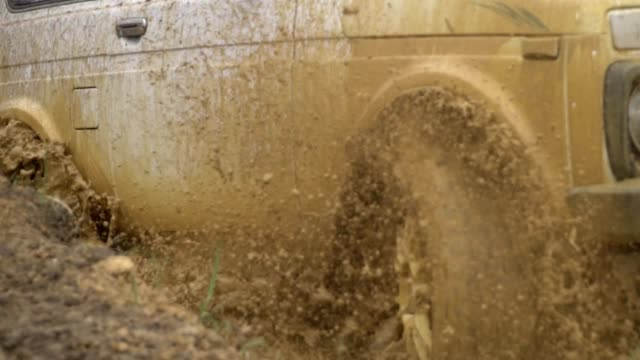 Beautiful car in rough terrain. A powerful SUV is towed in a deep puddle. Extreme driving conditions in the countryside. Flying from under the wheels of spray and dirt