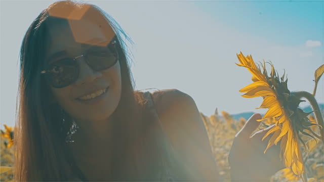 Beautiful Carefree Asian Young Woman Smiling Happily in Sunflowers Field video