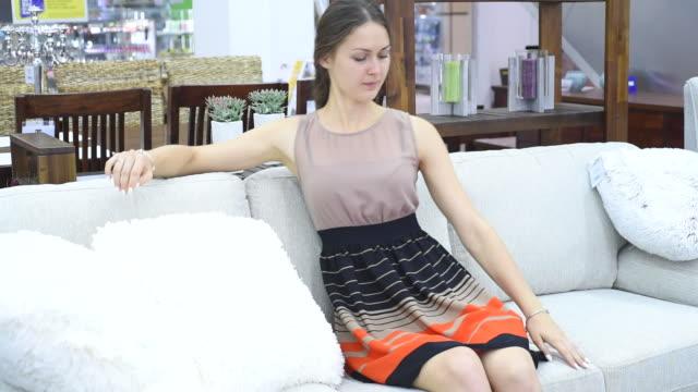 beautiful carefree woman chooses sofa video