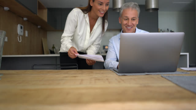 Beautiful caucasian couple at home paying bills using laptop while talking Beautiful caucasian couple at home paying bills using laptop while talking and smiling mid adult stock videos & royalty-free footage