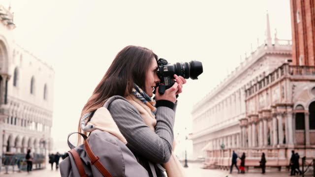Beautiful Caucasian freelance journalist with camera taking photos of ancient buildings at San Marco square, Venice.
