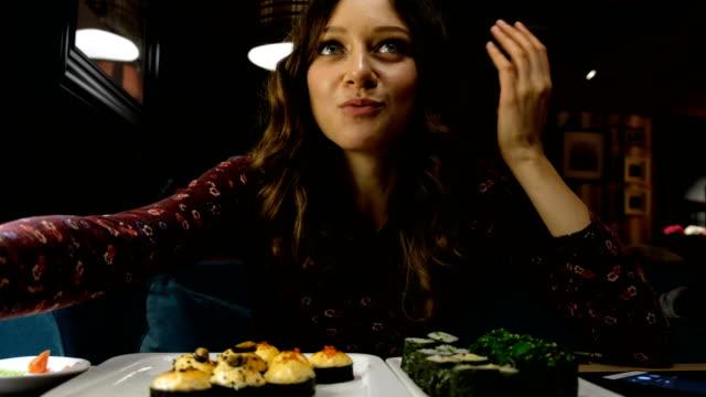 schöne frau kaukasischen essen sushi in ein japanisches restaurant und etwas interessantes erzählt seiner freundin gegenüber - japanisches essen stock-videos und b-roll-filmmaterial