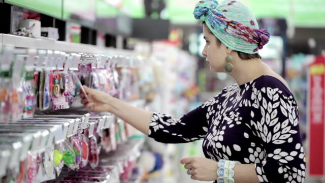 beautiful caucasian woman selects a barrette in the shopping centre - аксессуар для волос стоковые видео и кадры b-roll