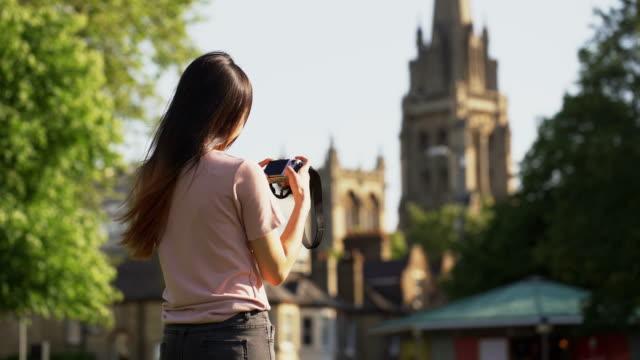 beautiful caucasian women take a photo with camera at park - tematy fotograficzne filmów i materiałów b-roll
