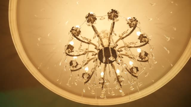 Beautiful chandelier on the ceiling of the restaurant, the rotation of the camera