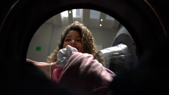 Belle clientèle gaie à une laverie automatique, chargement de la machine à laver en souriant - Vidéo