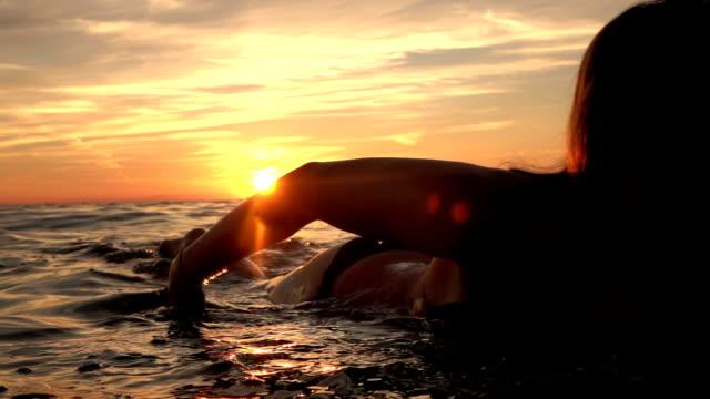 close up: beautiful cheerful girl paddling on surfboard at golden sunset - pesche bambino video stock e b–roll
