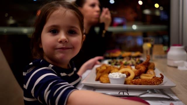 母と食事を楽しむ美しい子供 - 食事する点の映像素材/bロール