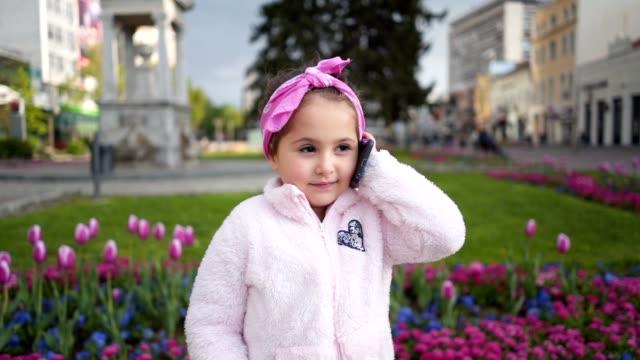 vackra barn pratar på en mobil telefon - endast flickor bildbanksvideor och videomaterial från bakom kulisserna