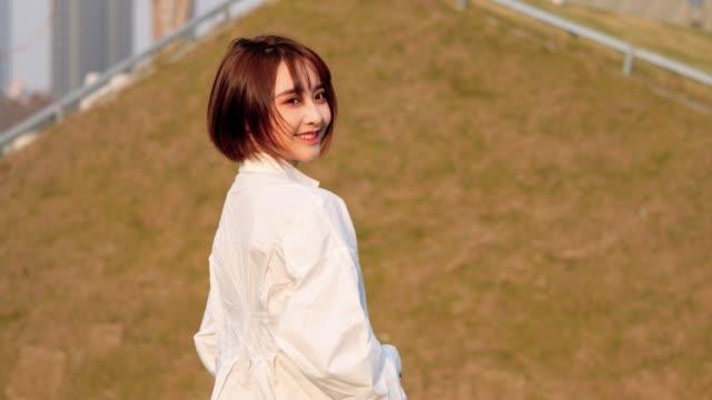 stockvideo's en b-roll-footage met mooie chinese meisje in wit shirt kijken terug en glimlachend naar camera in winderige en zonnige dag, zoete glimlach en cute blink, 4k film, slow motion. - oost azië