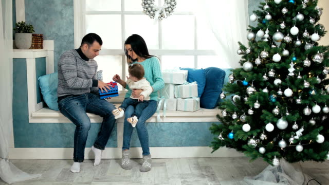 Beautiful christmas happy family with little girl in knitted sweaters sitting on the windowsill video