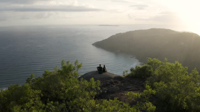 vídeos de stock, filmes e b-roll de tiro de estabelecimento aéreo cinematográfico bonito que aproxima um par assentado em uma caminhada pico ponto de uma montanha tropical da floresta que revela um cenário bonito do oceano da praia no fundo - largo descrição geral