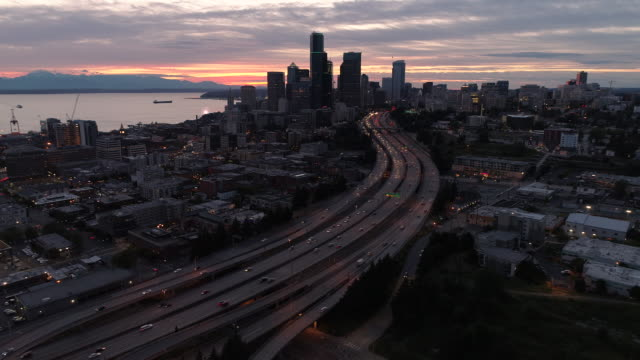 Beautiful Cityscape Aerial with Pink and Orange Sunset on City by Ocean and Mountains video