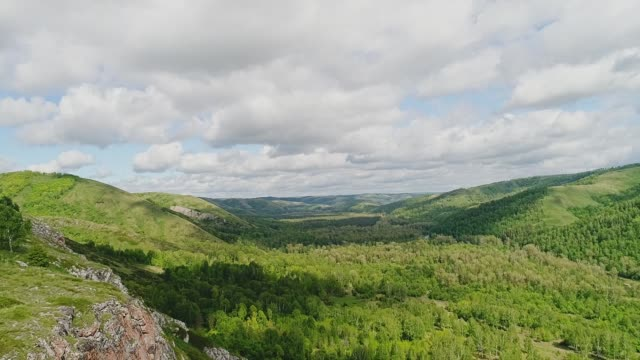 a beautiful cliff above a green valley in the mountains. blue sky - quadcopter filmów i materiałów b-roll
