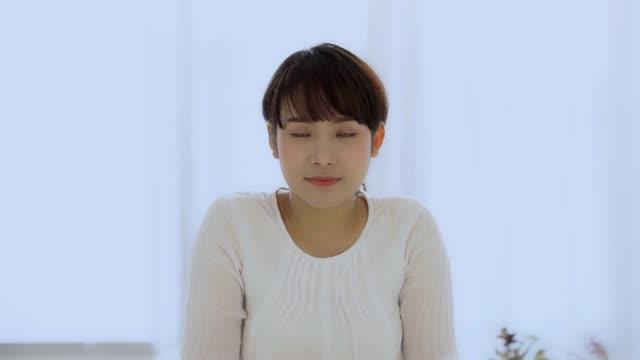 美しいですクローズアップ肖像画若いですアジアの女性とともに笑顔と笑いとともにベッドルーム, 女の子見ていますとともにカメラで幸せと面白い, スローモーション. - 人の肌点の映像素材/bロール