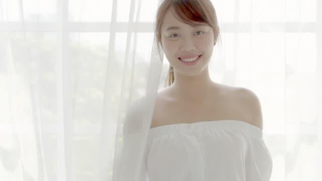 stockvideo's en b-roll-footage met mooie close-up portret jonge aziatische vrouw met glimlachen en lachen in de slaapkamer, azië meisje blij te kijken naar camera met vrolijke en grappige, slow motion, gezondheidszorg en wellness concept. - photography curtains