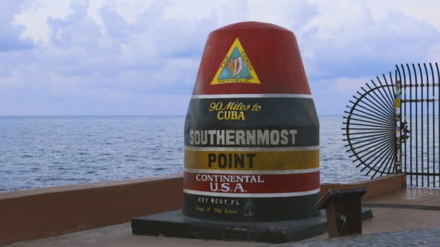 Beautiful closeup view of Southernmost Point Buoy on blue water of Atlantic OCean and blue sky background. Tourist attraction. Key West, Florida. USA. Beautiful closeup view of Southernmost Point Buoy on blue water of Atlantic OCean and blue sky background. Tourist attraction. Key West, Florida. USA. florida us state stock videos & royalty-free footage