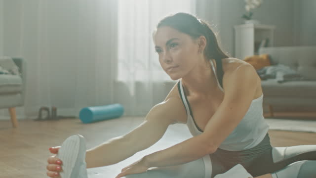 Beautiful Confident Fitness Girl in an Athletic Workout Clothes is Doing Stretching Yoga Exercises in Her Bright and Spacious Living Room with Cozy Minimalistic Interior.