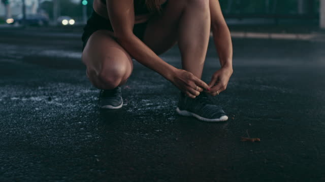 Beautiful Confident Fitness Girl in Black Athletic Top and Shorts Ties Shoelaces and Starts Running. She is in an Urban Environment Under a Bridge with Cars in the Background.
