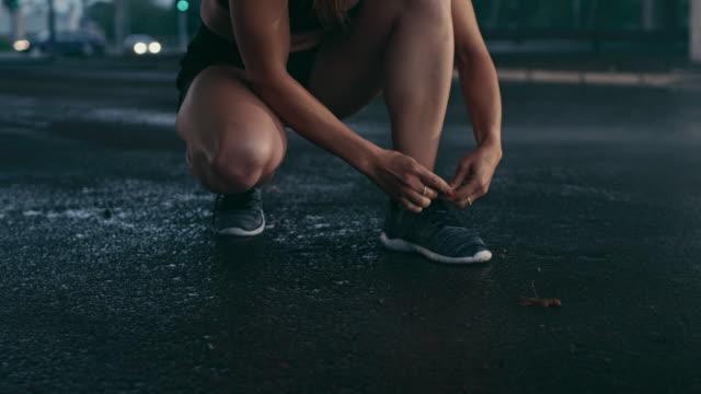bella ragazza di fitness fiducioso in black athletic top e pantaloncini cravatte shoelaces e inizia a correre. si trova in un ambiente urbano sotto un ponte con le auto sullo sfondo. - annodare video stock e b–roll